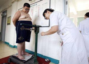 A 16-year old boy weighing 138 kg stands on the scale as a nurse documemts his weight